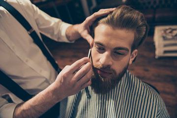 Close up cropped photo of a hairdresser`s work for an attractive young man at the barber shop. He is doing styling of his beard, shaving it with straight razor