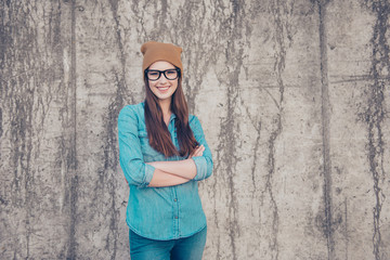 Attractive young girl student is standing on the concrete wall`s background outdoors, smiles, with crossed hands. She is wearing casual jeans outfit and brown hat, glasses