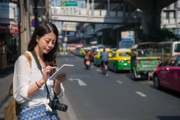 Chinese woman using tablet while walking