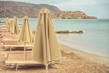 Deserted beach with sun umbrellas and sun beds