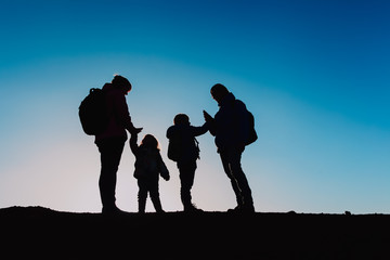 Silhouettes of family with two kids hiking at sunset