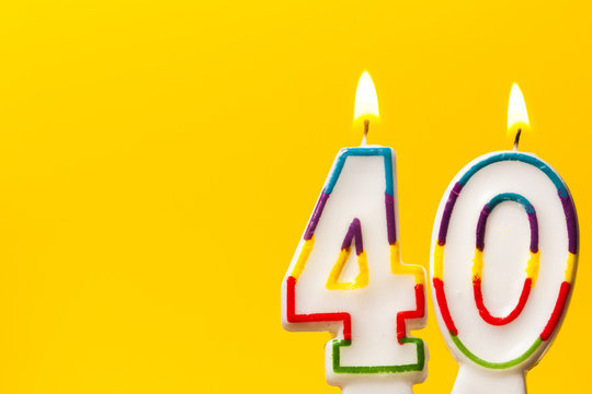 Number 40 birthday celebration candle against a bright yellow background