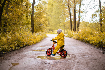 Little girl in yellow waterproof clothes with bike near a puddle