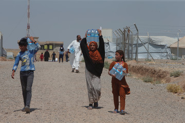 Displaced people, who fled from their homes carry bottles of water at a refugee camp
