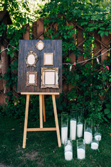 frames for gests list on wooden background, white candles on a grass