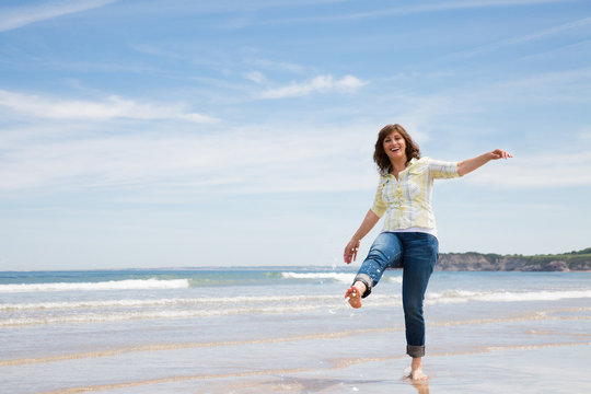 Playful middle aged woman on the beach