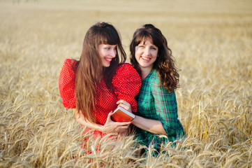 Two cheerful women in a wheat field at sunset in a blue and red long air dress.