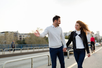 Happy young couple walking hand in hand