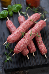 Close-up of raw fresh cevapcici or skinless beef sausages on skewers, selective focus, studio shot
