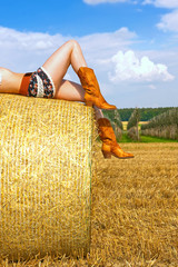 A lazy cowgirl lies on a hay bale and relaxes in the summer sun.