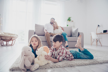 Leisure together. Happy family of four is enjoying at home, small kids are playing with toys, parents are on the sofa, hugging