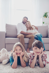 Four cheerful relatives. Happy parents and thier small cute kids, at home, all smiling, looking in a camera
