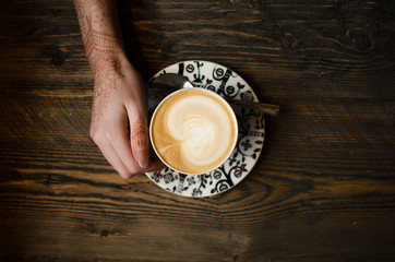 Cropped Hand Holding Coffee Cup At Table