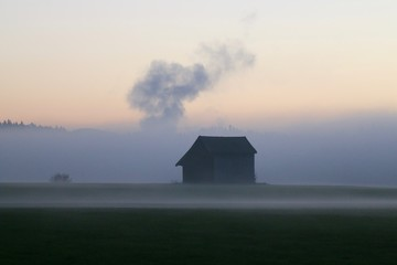 Barn On Field Against Sky During Foggy Weather