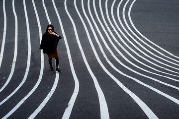 Full Length Portrait Of Young Woman Standing On Striped Asphalt