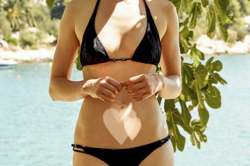 Midsection of woman in bikini standing outdoors