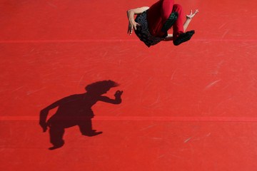 High Angle View Of Man Performing Somersault With Shadow On Red Floor