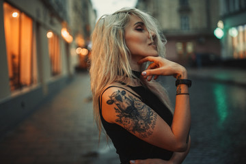 Young woman portrait with tattoo on shoulder standing on city street in evening.