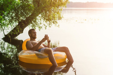 A man siting on an inflatable ring in the water and holding a smartphone. Young man relaxing in a rubber ring at dawn, the free space.