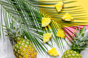 Pineapple and palm branch on wooden desk background top view