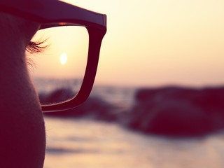 Close-Up Of Man Wearing Eyeglasses On Beach During Sunset