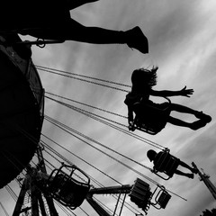 Low Angle View Of People At Chain Swing Ride Against Cloudy Sky