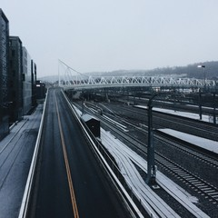 Elevated Road Over Railroad Tracks In City Against Sky