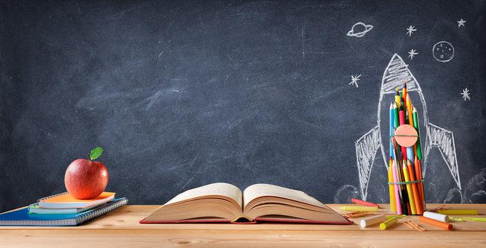 Start School Concept - Supplies On Desk And Rocket Drawn On Blackboard