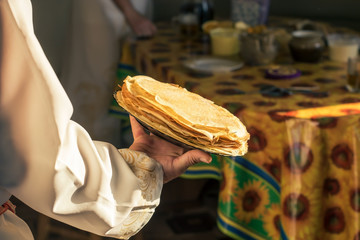 A man in a white national Slavic costume holds a plate of pancakes in his hand. Russian national food. Maslenitsa. Shrovetide