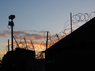 barbed wire and security camera with evening sky and sunset