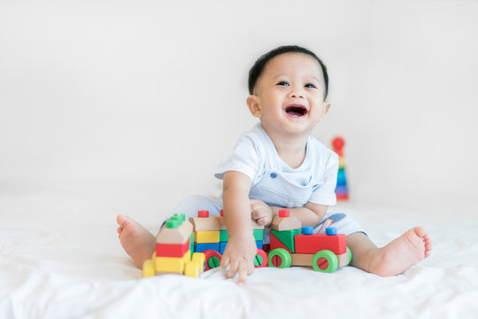 Adorable Asian baby boy 9 months sitting on bed and playing with color wooden train toys at home..