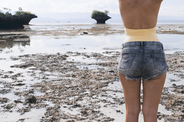 Woman in boho shorts and swimsuit on beach. Seashore and mountains on low tide.