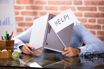 Businessman Covering His Head With Laptop Asking Help