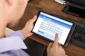 Businessman Filling Survey Form On Digital Tablet
