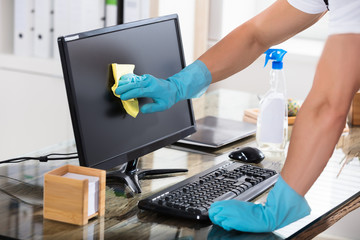 Close-up Of A Janitor Cleaning Computer Screen