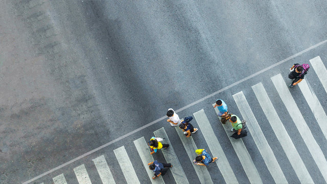 the busy city crowd move to pedestrian crosswalk on businees traffric road (Aerial photo, top view)