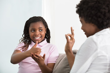 Deaf Mother Talking Sign Language With Her Daughter