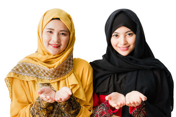 Portrait of two young muslim women on a white background.