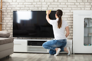 Woman Wiping The Television Screen At Home