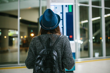 Young girl traveler with a backpack in a hat looks at the information board at the airport. Getting information about the flight. Transfer.
