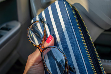 Closeup of woman's hand holding wallet and glasses waiting in the car at a drive thru