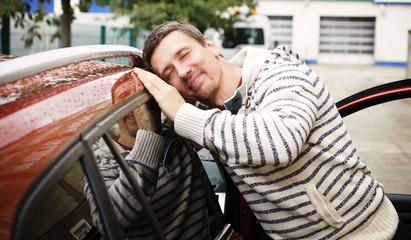 junger Mann ist verliebt in sein Auto