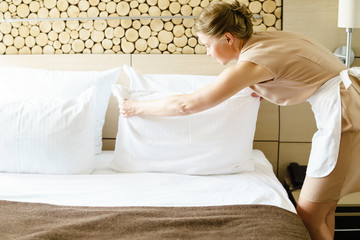 Chambermaid making a bed in a hotel room.