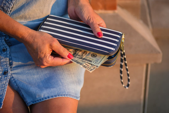 woman taking cash out of her wallet