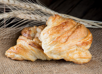 Tasty croissants on wooden background.