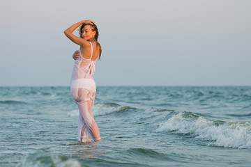 Sexy girl on the beach. Sexy girl in the ocean waves. fashion portrait women on the sea. beautiful girl in a wet white dress. Girl in the sea