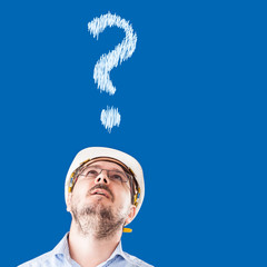 Worker with construction helmet look up with misunderstanding face on blue background and question symbol