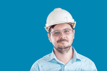 Handsome 30 years old task manager with construction helmet and glasses on blue background