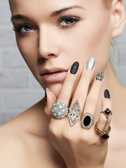 beauty face.woman's hands with jewelry rings