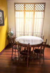 Wooden round table and chair chiness style near window have ray of light on wood floor and yellow wall have lotus chiness picture